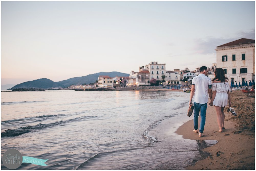 The couple walk hand-in-hand across the beach with Santa Maria di Castellabate in the background.