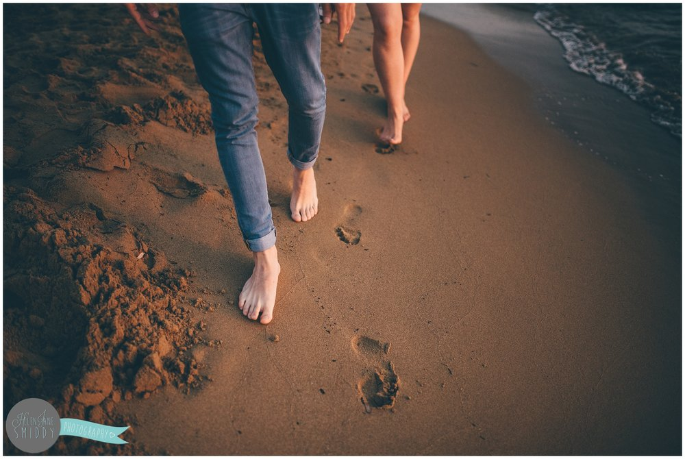 Sabrina and Dom make footprints in the sand during their engagement shoot in Italy.