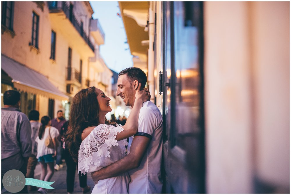 The gorgeous couple kiss against a wall in the old Italian town of Santa Maria di Castellabate.