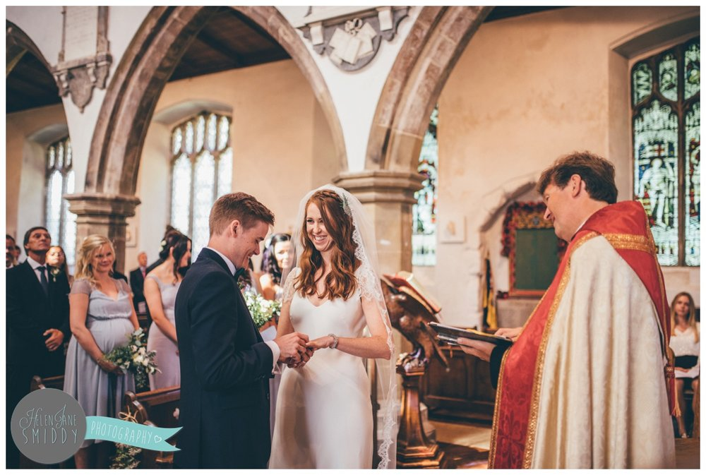 Cheshire wedding photographer shoots wedding in Norfolk, the couple exchange rings in church.