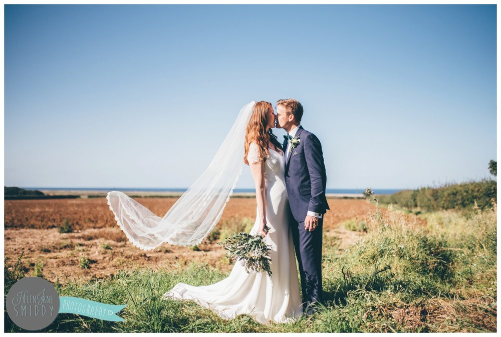 Newlyweds share a kiss at their stunning Norfolk venue on a sunny September day.