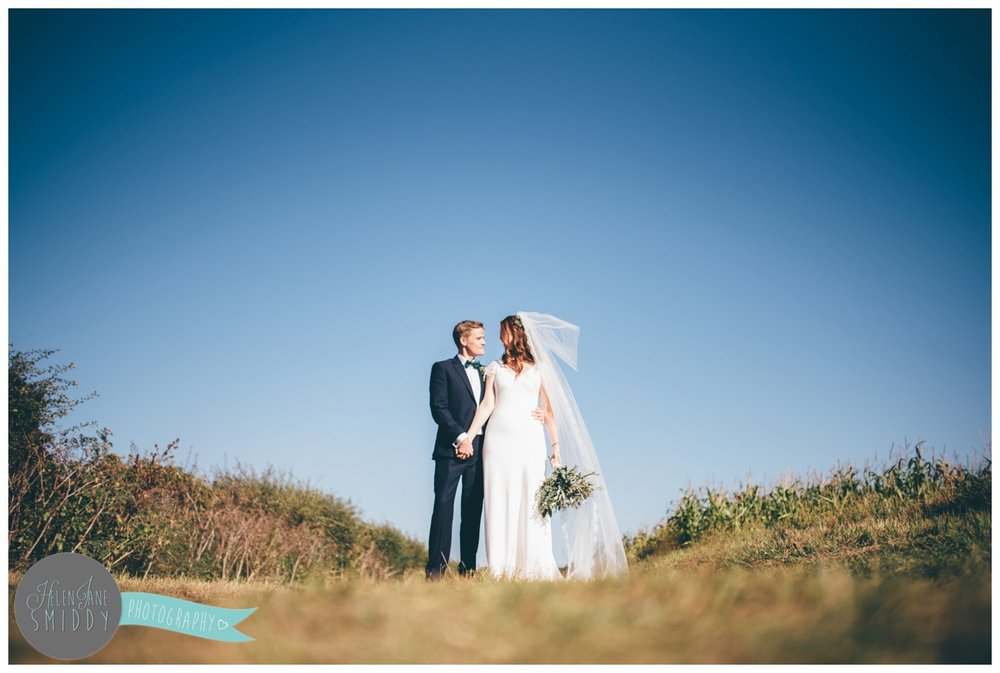 Couple kiss in front of beautiful blue skies in Norfolk.