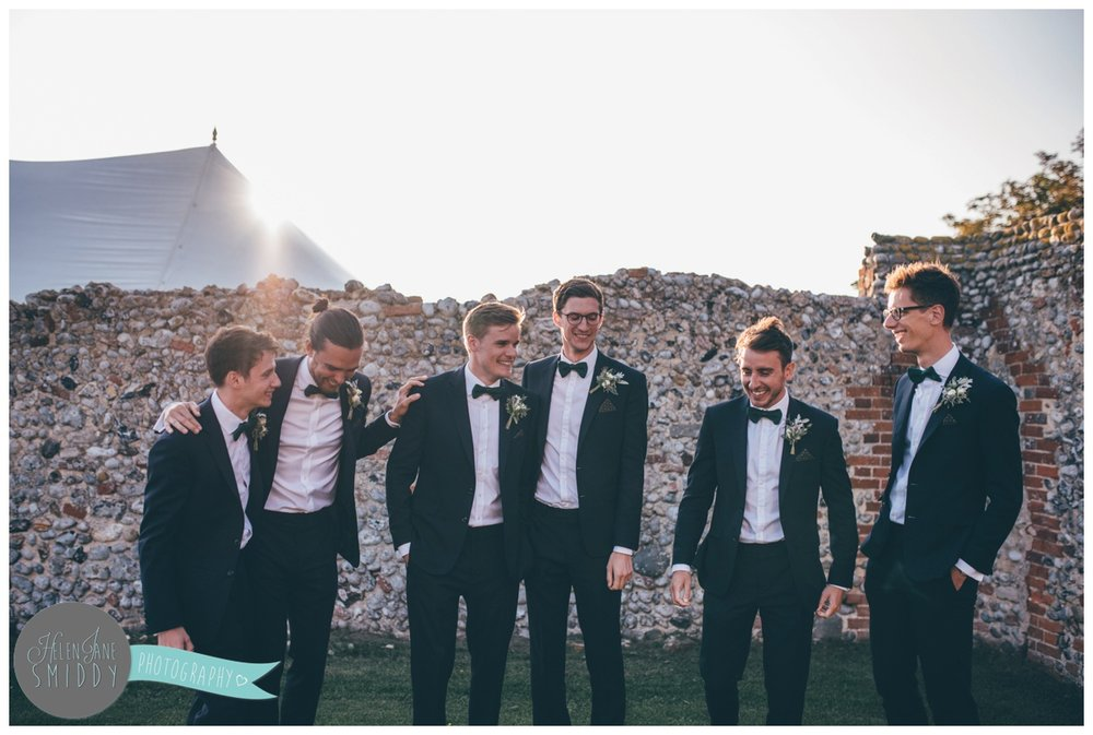 Groomsmen joke together at a Barn Drift wedding in Norfolk.