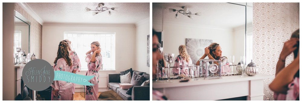 The bridesmaids admire their hair and make-up in the mirror on the wedding morning.