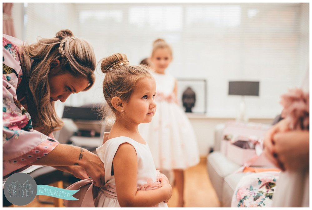 One of the older bridesmaids fastening a cute little flowergirl into her dress.