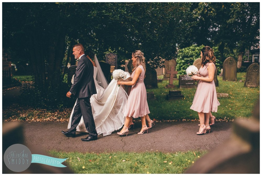 Father of the bride leads his daughter and the bridal party into church.