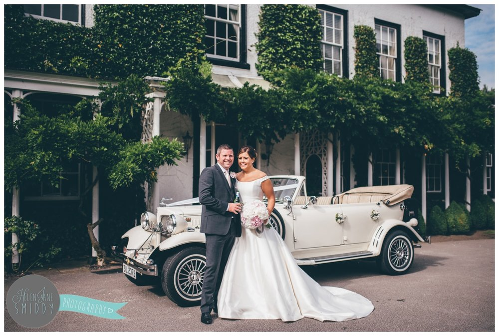The newlyweds stand in front of their car outside Statham Lodge wedding venue.