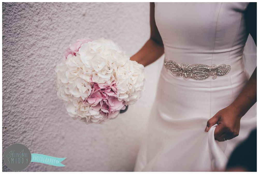 The bride carries her stunning hydrangea bouquet.