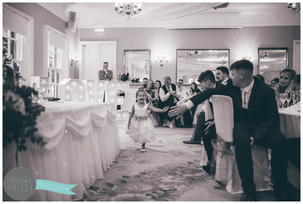 Flower girl runs around whilst the wedding guests listen to the speeches.
