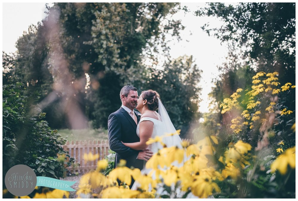 The newlyweds laugh together in the pretty gardens at Statham Lodge.