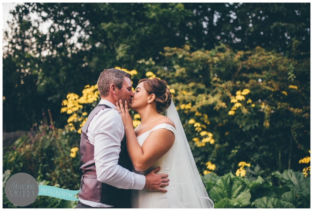 The bride and groom share a kiss at Statham Lodge.