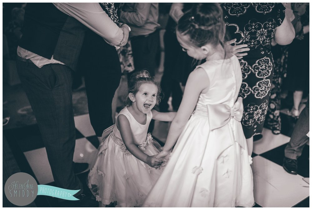 The flower girls have fun dancing away at the wedding at Statham Lodge.