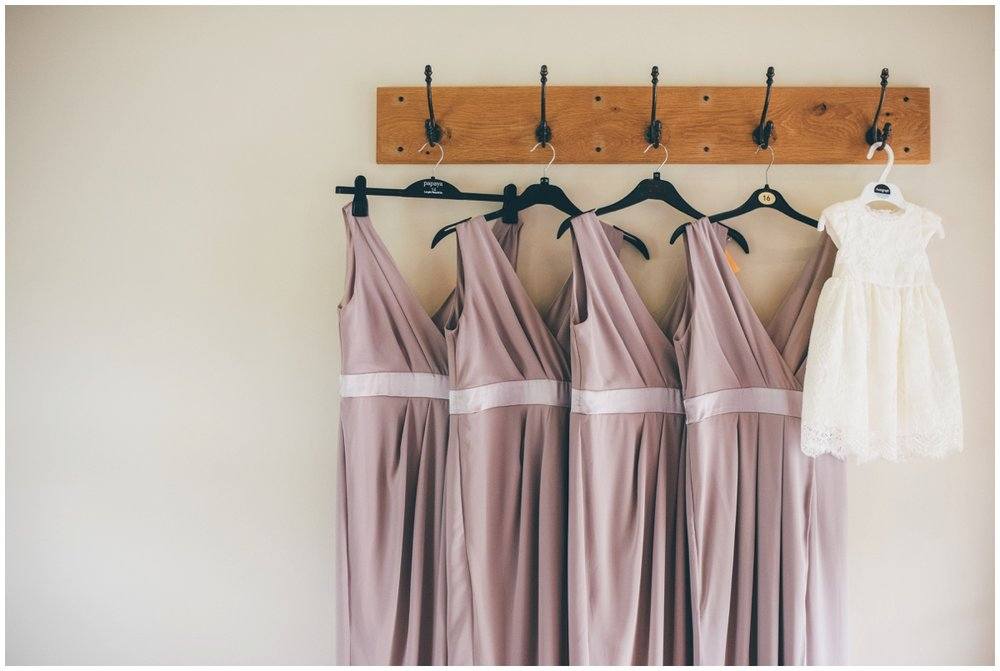 The bridesmaids dresses hung up in the bridal suite at The Ashes wedding barn in Staffordshire.