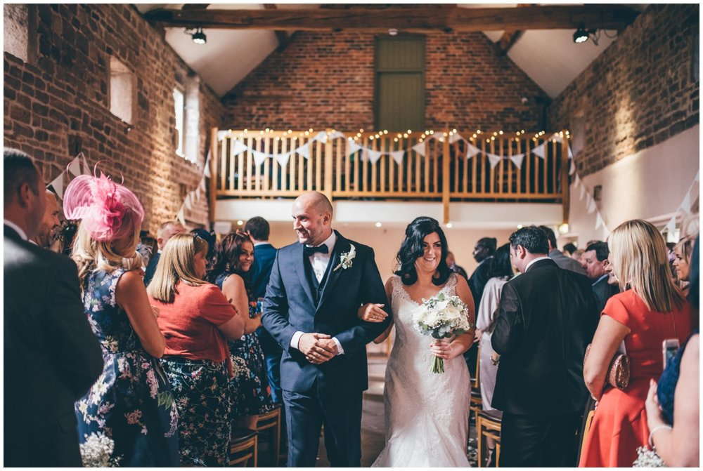 The new husband and wife walk down the aisle together  at The Ashes wedding barn in Staffordshire.