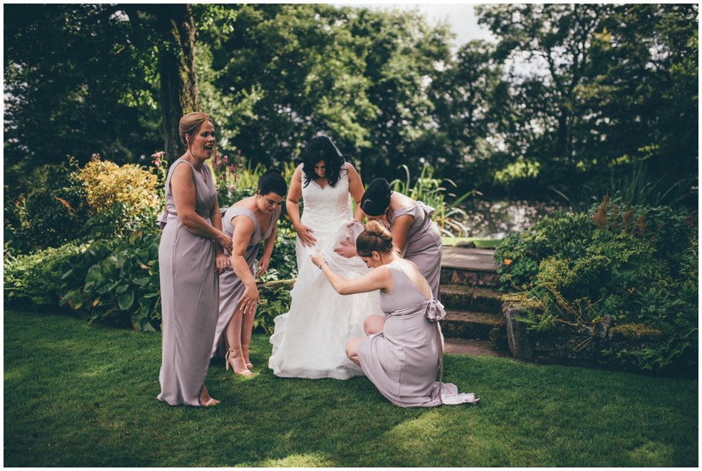 The bridesmaids help Amy with her dress in the gardens at The Ashes wedding barn in Staffordshire.