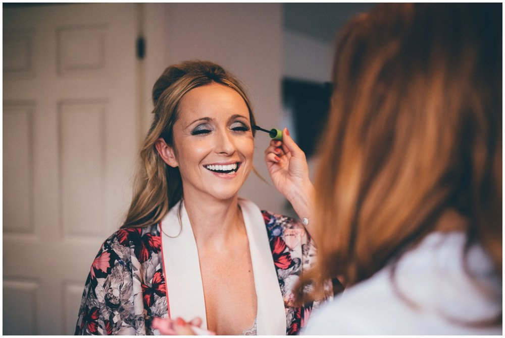 Manchester Bride laughs as the make-up artist makes a joke.
