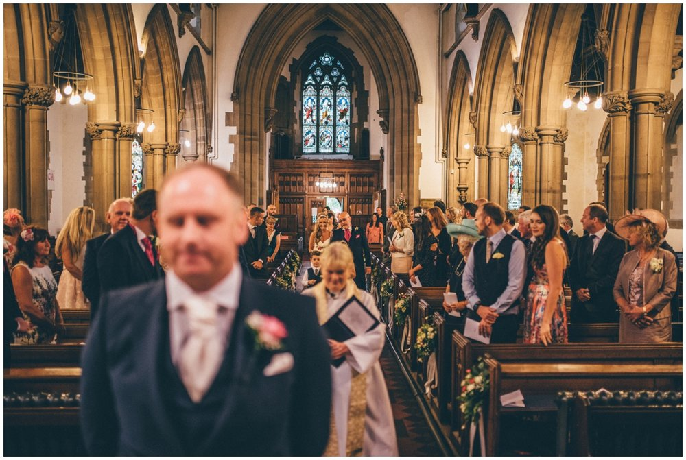 The vicar of St Mark's Church in Worsley leads the bridal party in to the groom.