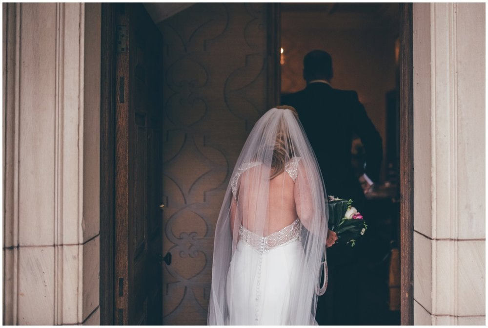 The beautiful detailed back of the bride's wedding dress shows as she walks nto her wedding venue, Willington Hall in Cheshire.