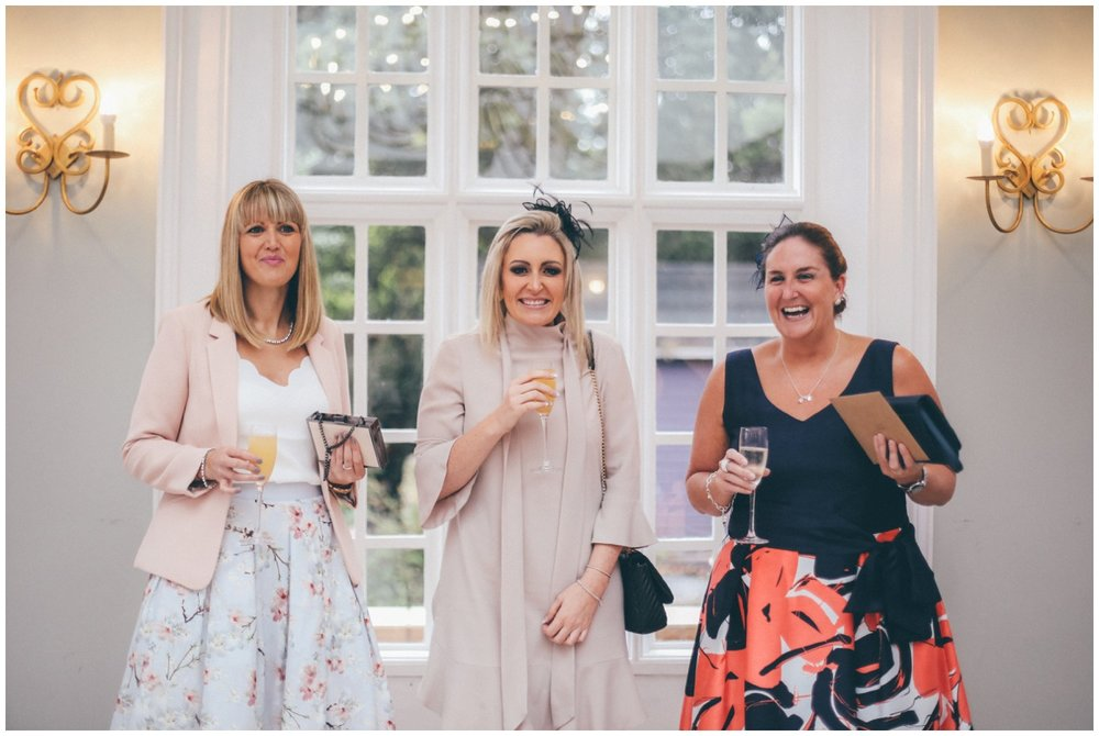 Women smiling at their Cheshire wedding photographer in the orangery at Willington Hall in Cheshire.
