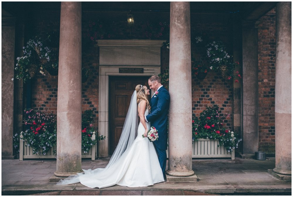 The new husband and wife share a kiss at the beautiful entrance to Willington Hall in Tarporley.