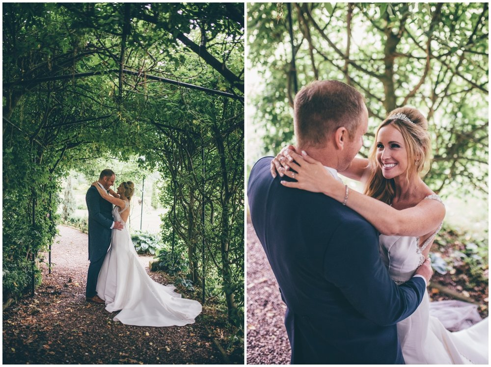 The happy couple embrace amidst the greenery in the beautiful gardens at Willington Hall in Cheshire.