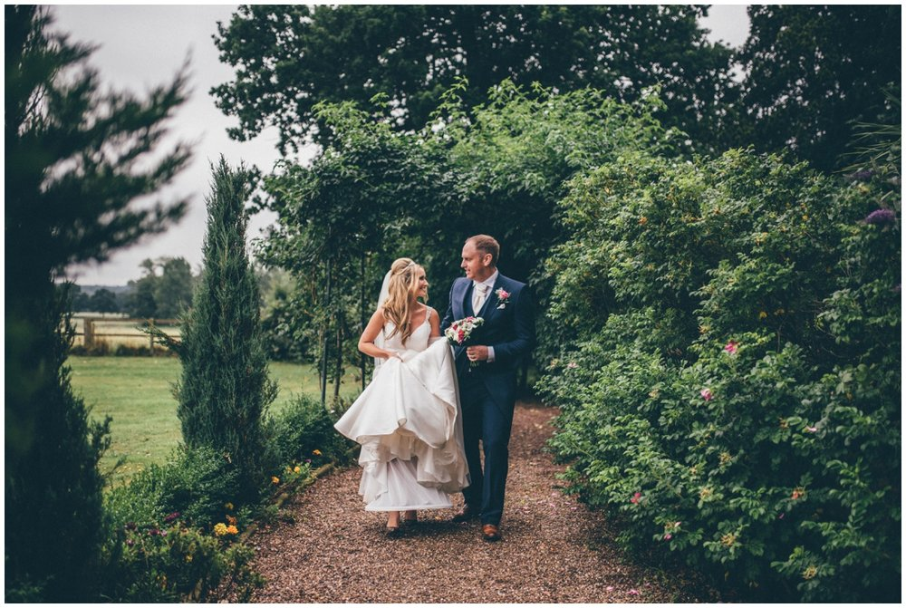 Happy groom helps his new wife walks through the pretty gardens.