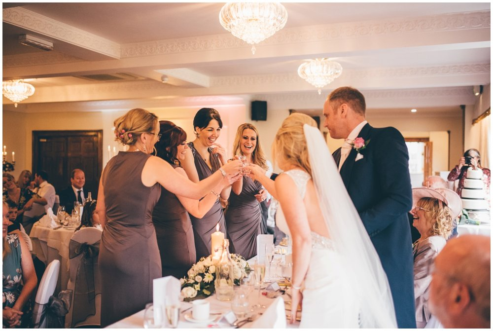 The bride does a shot of sambuca with her new husband and bridesmaids at Willington Hall during the speeches.