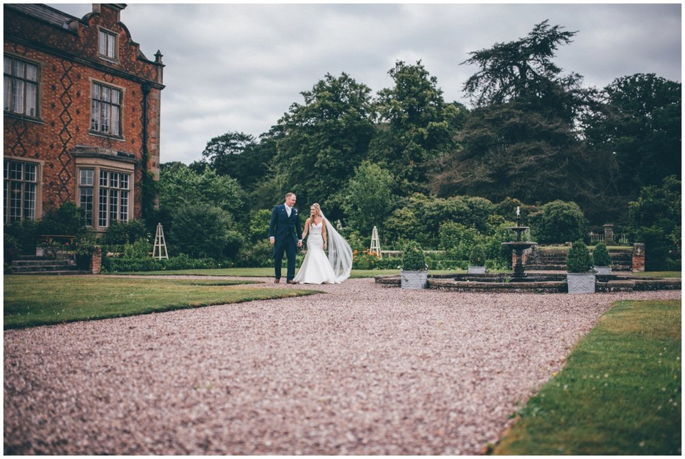 The newlyweds walk hand in hand through the grounds of their beautiful wedding venue in Tarporley, Cheshire.