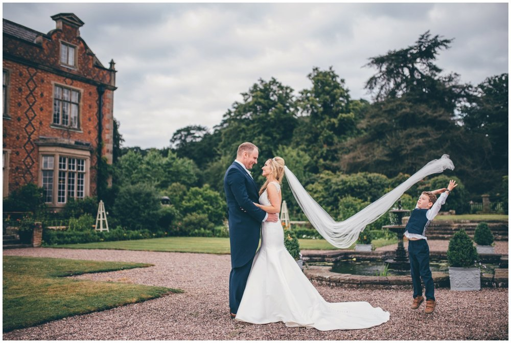 The adorable little pageboy helps the Cheshire wedding photographer by throwing the veil up in the wind.