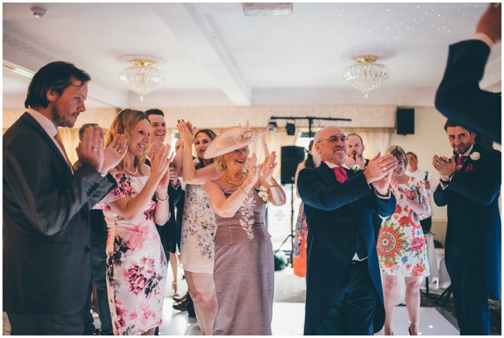 The wedding guests all cheer the bride and groom during their First Dance at Willington Hall in Cheshire.