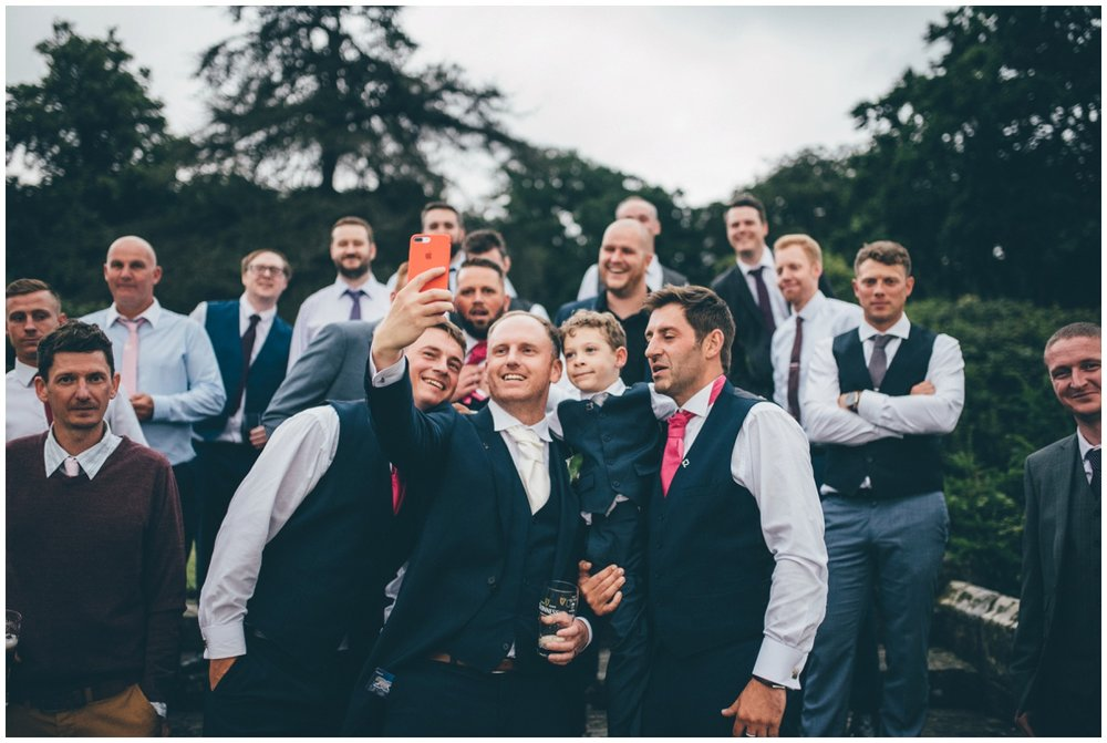 The groom takes a selfie with all the guys at his wedding in the beautiful gardens at Willington Hall.