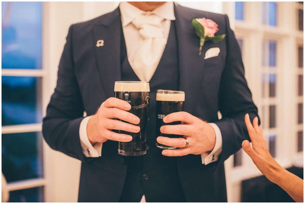 The groom holds his own pint of Guinness and his wife's half pint of Guinness at their wedding reception.