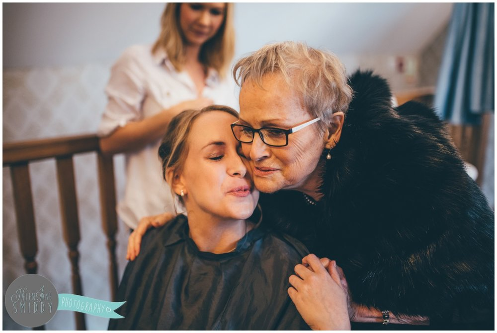 The bride's grandma gives her a good luck kiss on the morning of her wedding.