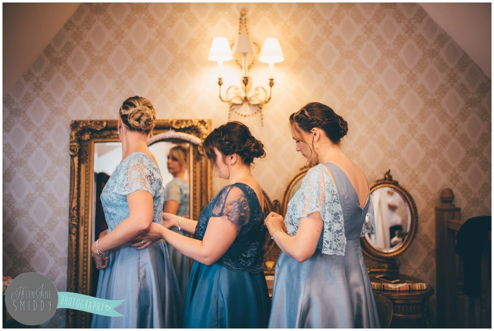The bridemaids help each other to dress on the wedding morning at Bassmead Manor.