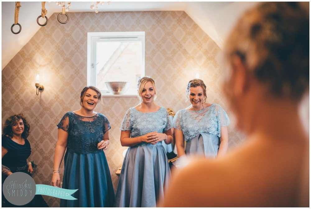 Beautiful bridesmaids see the bride for the first time in her wedding gown at Bassmead Manor.
