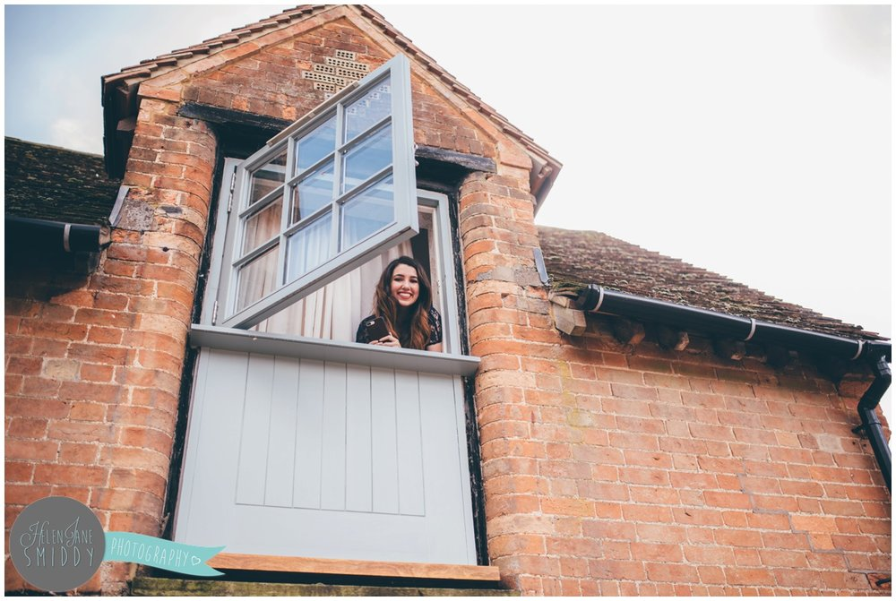 Bridesmaid pops her head out of the window at Bassmead Manor barns.