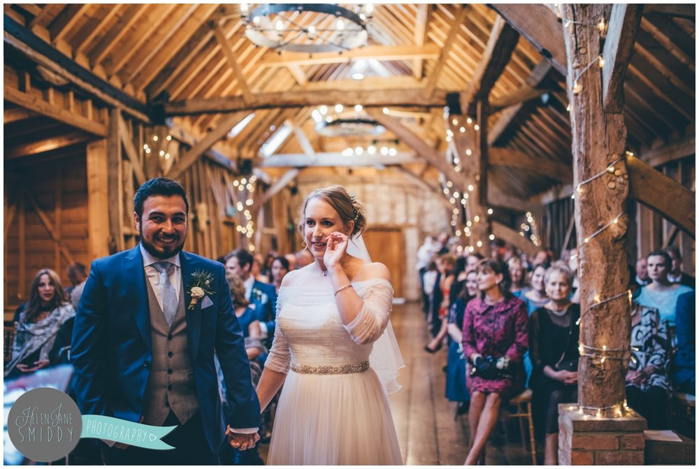 The bride and group take their vows at Bassmead Manor Barns in Cambridge.