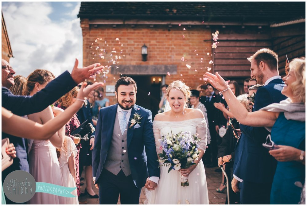 Beautiful confetti is thrown over the bride and groom at Cambridgeshire wedding venue.