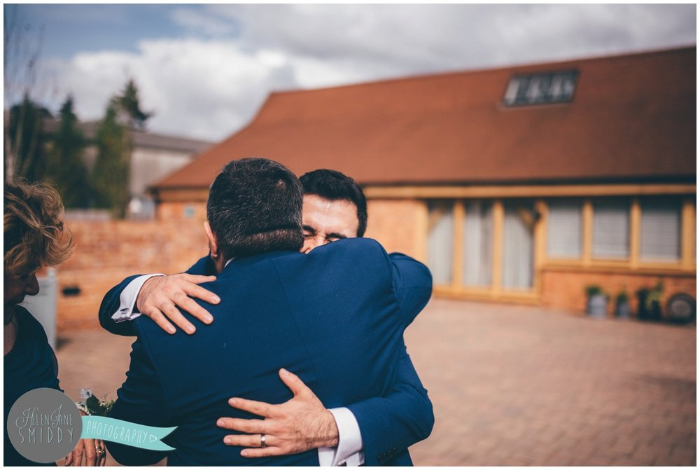 Groom hugs his Dad and celebrates his new marriage.