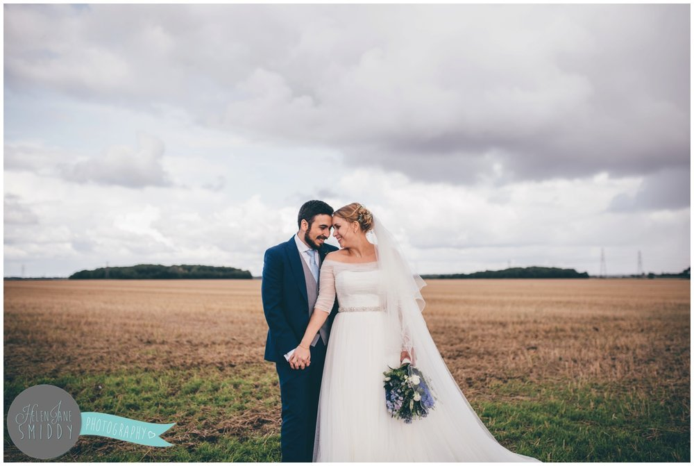 The couple share an intimate moment during their wedding photgraphs which were in a field at Bassmead Manor wedding barns.