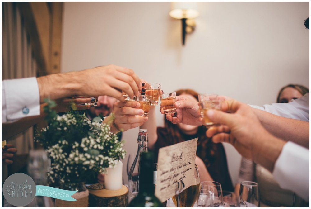 Wedding guests do shots of tequila during Wedding speeches at Bassmead Manor wedding barns.