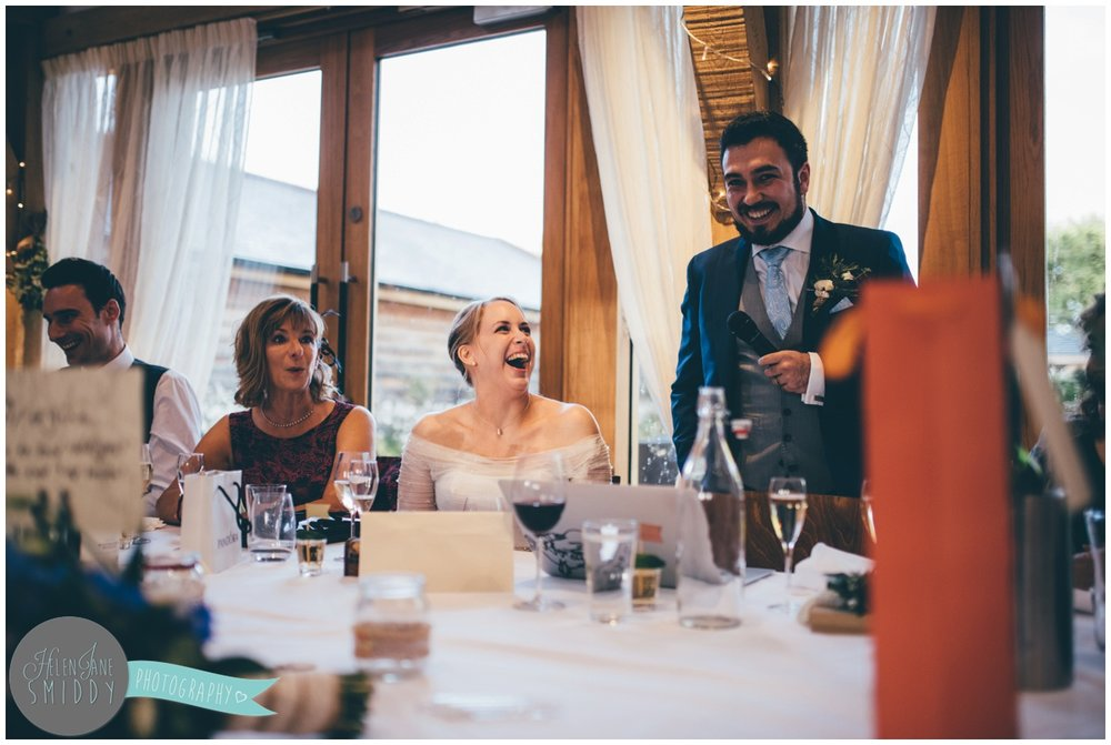 Bride laughs at her groom during Wedding speeches at Bassmead Manor wedding barns.