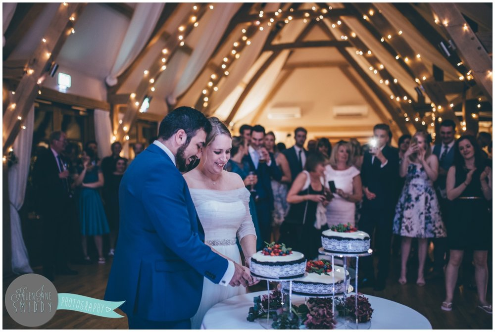 Bride and groom cut their homemade wedding cake at Bassmead Manor wedding barns.