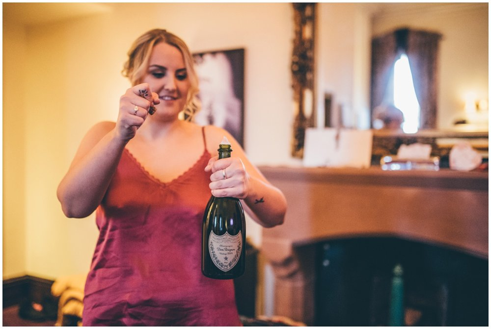 Bridesmaid opens a bottle of champagne on the wedding morning.