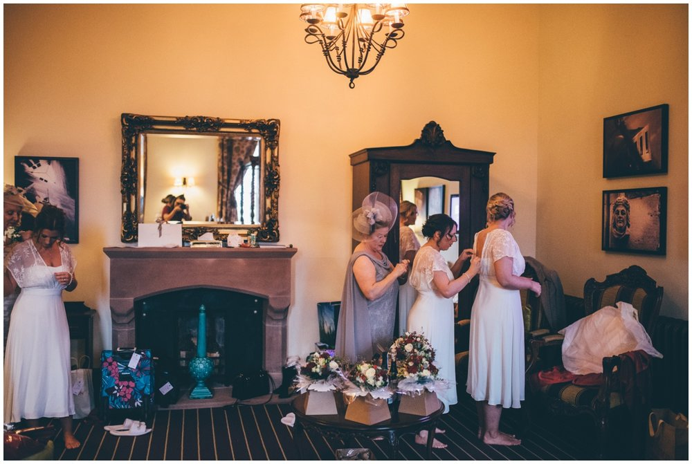 Bridesmaids all help each other dress before the wedding ceremony.