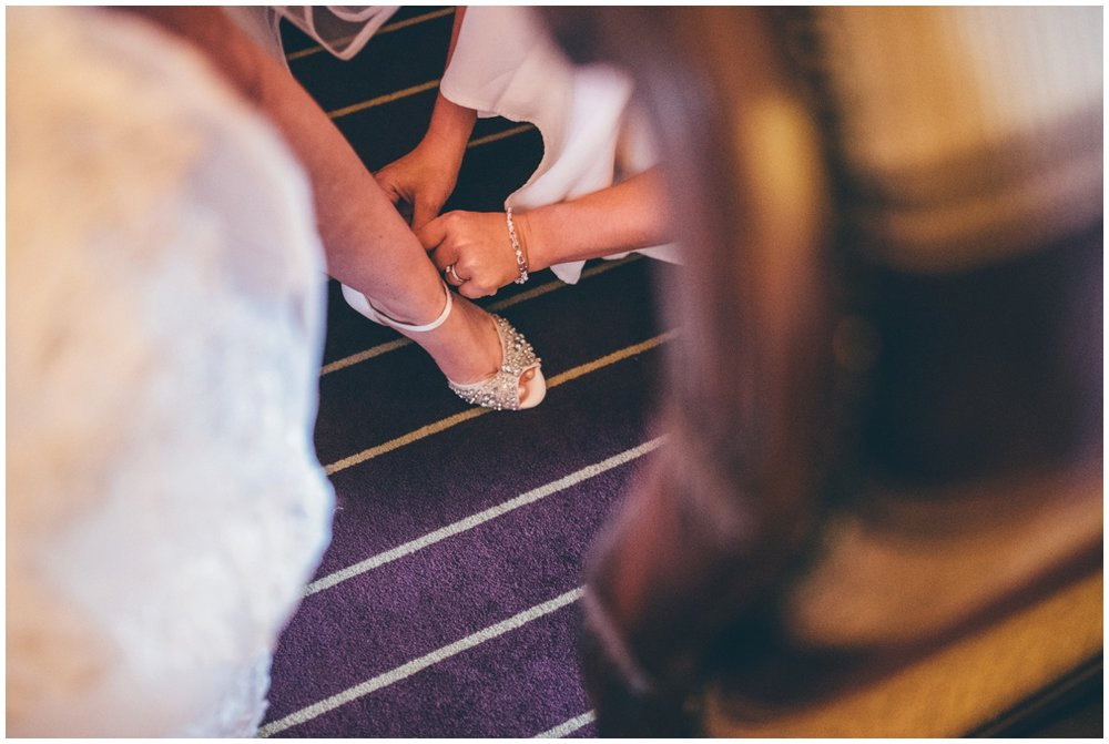 Maid of honour fastens the bride into her Jenny Packham wedding shoes.