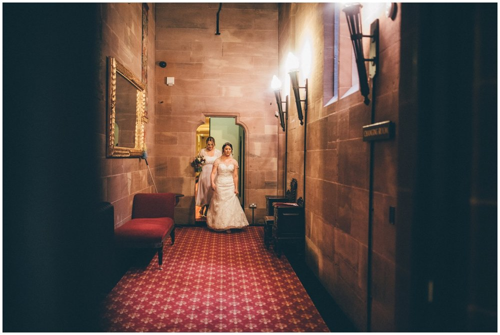 Bride leads her bridesmaids through the corridors at Peckforton Castle.