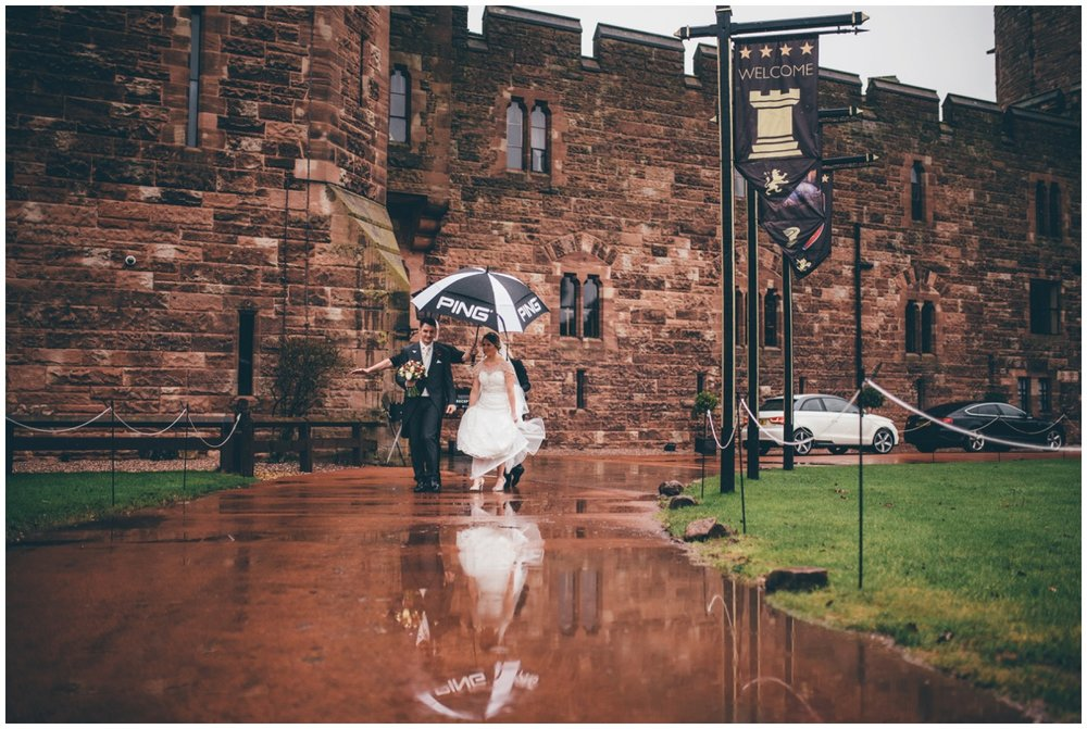 Sarah and Adam walk through the rainy grounds of Peckforton Castle.