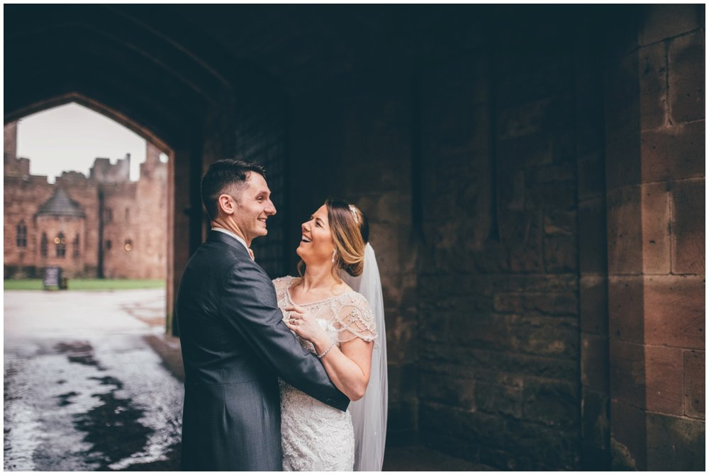 The bride and groom have their wedding photographs taken at the entrance of Peckforton Castle.