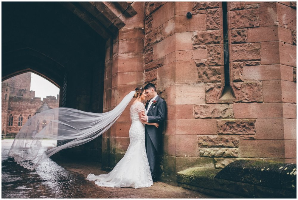 Stunning veil blowing in the wind at Peckforton Castle archway.
